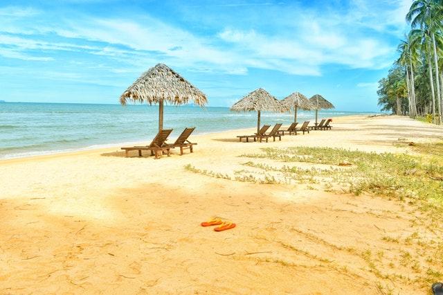 Odľahlá pláž so slnečníkmi a ležadlami pre turistov