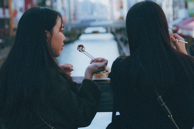 Dve ženy obedujú na ulici s paličkami