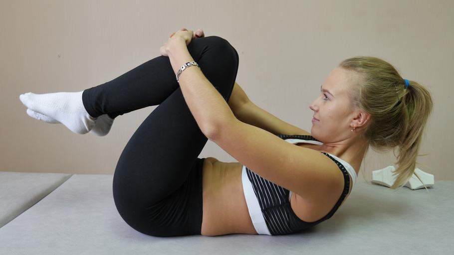 Žena cvičí cviky na chrbticu na sivom matraci.jpg