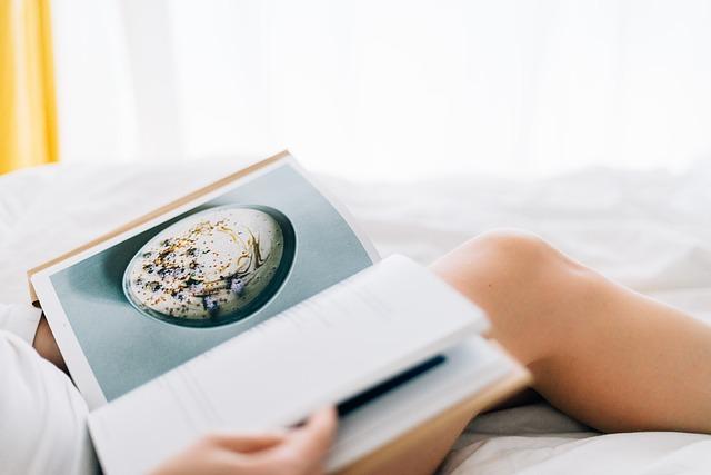 Žena sedí v posteli a prezerá si knihu s obrázkami jedla.jpg