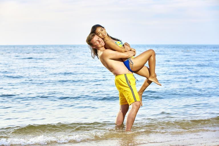 Muž zdvíha ženu na pláži.jpg