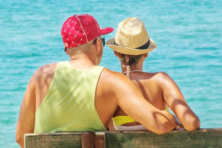 Zamilovaný pár sedí na lavičke pri vode.jpg