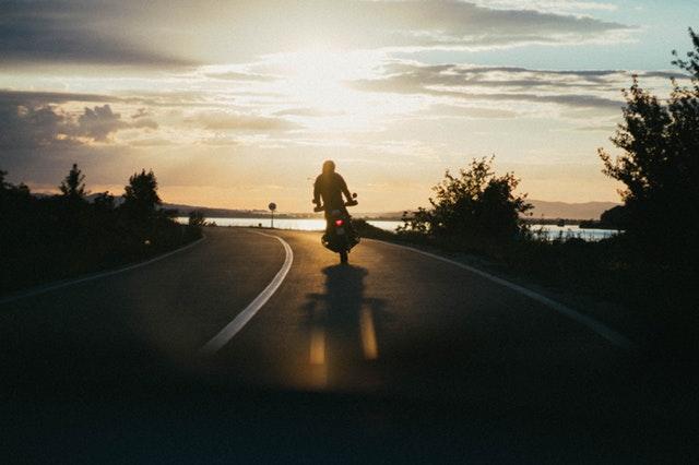 Človek v stoji šoféruje motorku pri západe slnka