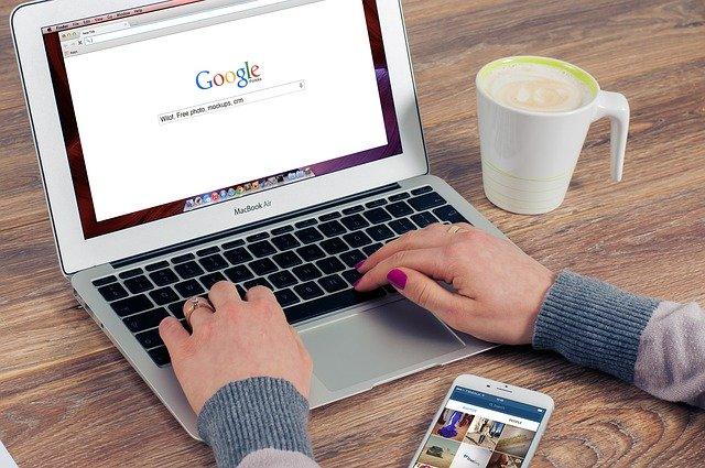 Žena píše na notebooku, vedľa ktorého má položený hrnček s kávou